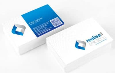 Icon Graphic Design Adelaide - Realise IT Solutions business card design displayed on 2 small stacks of cards.